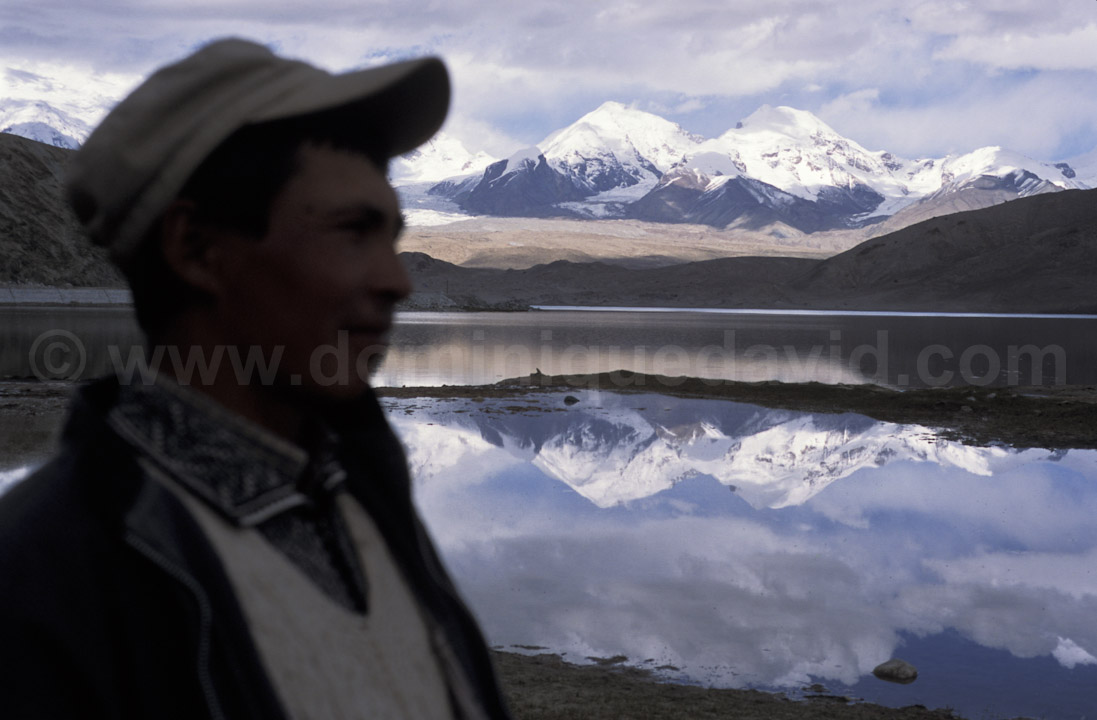 Lake Karakol (China) - Kyrgyz shepherd standing in front of Karakul Lake and snow-capped mountains - Photo by Dominique David